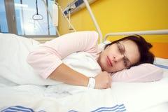 Traurige Frau von mittlerem Alter, die im Krankenhaus liegt Stockbild