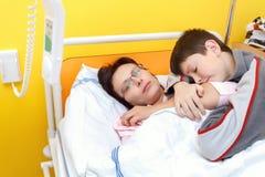 Traurige Frau von mittlerem Alter, die im Krankenhaus mit Sohn liegt Stockfoto