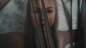 Traurige Frau, wenn schwarzer Schleier auf weißem Wandhintergrund beklagt wird stock video footage