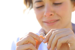 Traurige Freundin, die ihren Verlobungsring schaut Lizenzfreies Stockfoto
