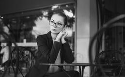 Traurige Geschäftsfrau, die im Café, Schwarzweiss sitzt Stockbild