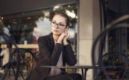 Traurige Geschäftsfrau, die im Café sitzt Stockfotos