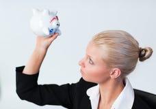 Traurige Geschäftsfrau, die Piggy Querneigung untersucht Lizenzfreies Stockbild