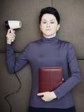 Traurige Geschäftsfrau liegt mit dem persönlichen Hand Organisator und hairdryer auf Sofa Stockfotos