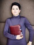 Traurige Geschäftsfrau liegt mit dem persönlichen Organisator, der auf braunem Sofa Hand ist Lizenzfreie Stockfotos