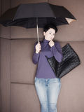 Traurige Geschäftsfrau liegt mit Regenschirm und ihrer Handtasche auf Sofa Lizenzfreies Stockbild