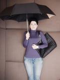 Traurige Geschäftsfrau liegt mit Regenschirm und ihrer Handtasche auf Sofa Lizenzfreie Stockbilder