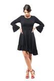 Traurige hübsche Frau im schwarzen Kleid mit den Händen auf den Taillen, die unten schauen Stockfotografie