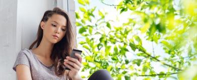 Traurige hübsche Jugendliche mit dem Smartphonesimsen Stockfotos