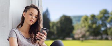Traurige hübsche Jugendliche mit dem Smartphonesimsen Stockbilder