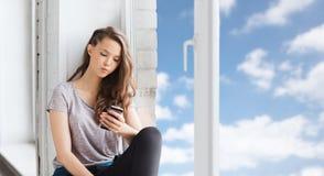 Traurige hübsche Jugendliche mit dem Smartphonesimsen Lizenzfreies Stockfoto