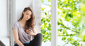 Traurige hübsche Jugendliche mit dem Smartphonesimsen Stockbild