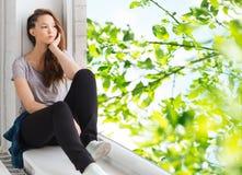 Traurige hübsche Jugendliche, die auf Fensterbrett sitzt Stockfotos