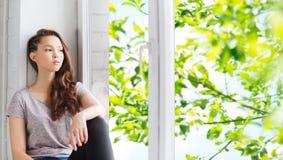 Traurige hübsche Jugendliche, die auf Fensterbrett sitzt Stockfoto