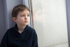Traurige 7 Jahre Jungenkind, die heraus das Fenster schauen Lizenzfreie Stockfotos