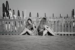 Traurige Jugendliche in der Ruhe auf dem Strand sprechend nicht nach dem Kampf Schwarzweiss Stockbilder
