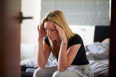 Traurige Jugendliche, die im Schlafzimmer sitzt, während Freund schläft Lizenzfreies Stockfoto
