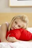 Traurige Jugendliche im Schlafzimmer, das Kissen umarmt Lizenzfreie Stockfotos