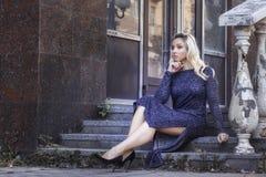 Traurige junge blonde Frau in der Lederjacke, die auf den Schritten sitzt Stilvolles Mode-Modell im Freien Stockfotos