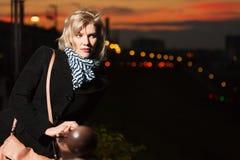 Junge Frau gegen eine Nachtstadt Stockbilder