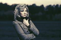 Traurige junge blonde Modefrau im klassischen Mantelgehen im Freien Stockfotografie