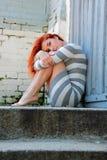 Traurige junge Frau auf den Treppen Stockbild