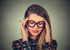 Traurige junge Frau in den Gläsern mit besorgtem betontem Gesichtsausdruck Stockfotos