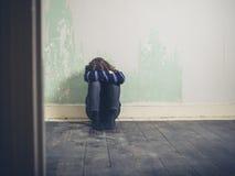 Traurige junge Frau, die auf Boden im leeren Raum sitzt Lizenzfreie Stockfotografie