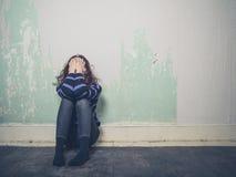 Traurige junge Frau, die auf Boden im leeren Raum sitzt Stockbilder