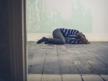 Traurige junge Frau, die auf Boden liegt Stockbilder
