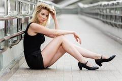 Traurige junge Frau, die auf dem Bürgersteig sitzt Stockbild