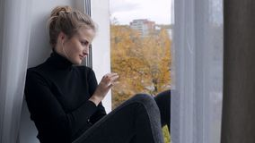 Traurige junge Frau, die auf Fensterbrett sitzt und Fenster betrachtet stock footage