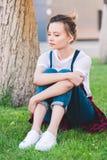 traurige junge Frau, die auf grünem Rasen sitzt stockfotos