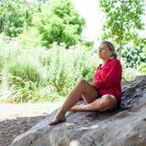 Traurige junge Frau, die auf riesigem Stein für Sommerfrische sitzt Stockfoto