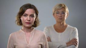 Traurige junge Frau, die in camera, strenge ältere Mutter hinten steht, Problem schaut stock footage