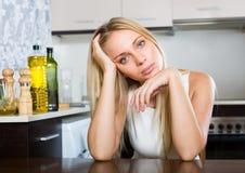 Traurige junge Frau, die an der Küche sitzt Lizenzfreie Stockfotografie