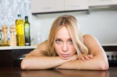 Traurige junge Frau, die an der Küche sitzt Stockfotografie