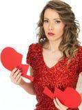 Traurige junge Frau, die ein defektes Valentinsgruß-Herz hält Stockfotos