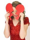 Traurige junge Frau, die ein defektes Valentinsgruß-Herz hält Lizenzfreies Stockbild