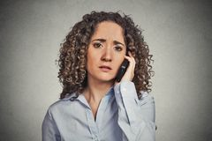 Traurige junge Frau, die am Handy spricht Stockbild