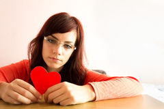 Traurige junge Frau, die Herz hält Stockbild