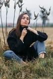 Traurige junge Frau, die im langen trockenen Herbstgras sucht für Einsamkeit und ruhige Ruhe von der Stadt, wolkiges Wetter sitzt Stockbilder