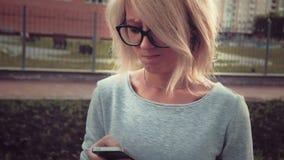 Traurige junge Frau, die im Parkbereich unter buldings unter Verwendung ihres simsenden Fühlens des Smartphone traurig steht stock footage