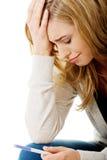 Traurige junge Frau, die Schwangerschaftstest hält stockfotografie