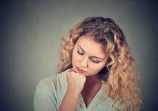 Traurige junge Frau, die unten schaut Stockfotografie