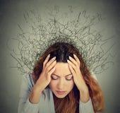 Traurige junge Frau mit besorgtem betontem Gesichtsausdruck und Gehirn, das in Linien schmilzt Stockbild