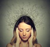 Traurige junge Frau mit besorgtem betontem Gesichtsausdruck und Gehirn, das in Linien schmilzt Stockfoto