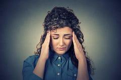 Traurige junge Frau mit dem besorgten betonten Gesichtsausdruck, der Kopfschmerzen hat Lizenzfreie Stockfotografie