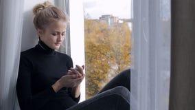 Traurige junge Frau mit dem Smartphone, der auf Fensterbrett sitzt stock video