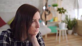Traurige junge Frau mit einer Brandnarbe auf ihrem Gesicht, das allein sitzt stock video